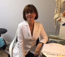 Stella Archer at her desk in her clinic